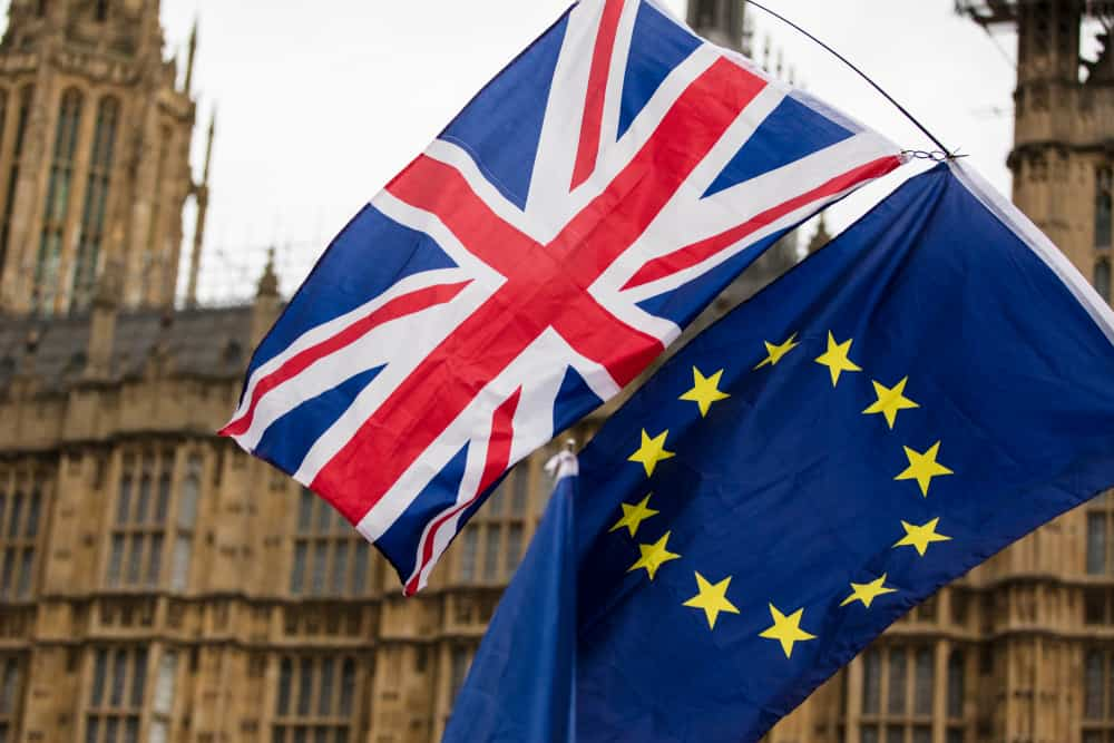Photo: The British flag and EU flag pictured flying with the UK Houses of Parliament in the background in London, UK.